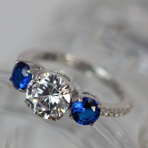 2018 Beautifully created Sapphires ring. Perfect bled of White Diamond simulant and two Blue beautifully created Sapphires. All stones are 5AAAAA level quality. Italian design and Italian origin High quality stones. 3X of Genuine Platinum plated with addi